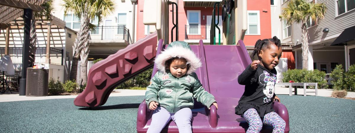 Two young children laughing and sliding down a double slide in a playground at the Cedars at Carver Park development in Galveston, Texas.