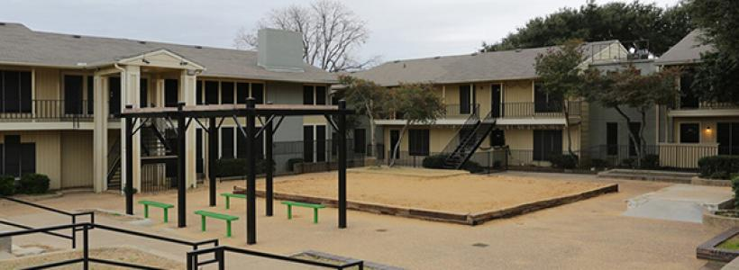 View of the courtyard with benches surrounded by two-story apartment buildings, with stairs leading up to the second floor and railings on the second floor.