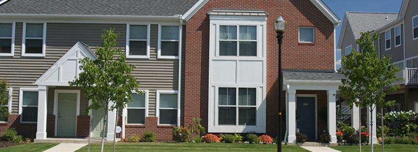 A row of two story town homes, the exterior is red, gray, and white.  Each has a covered patio and small lawn.