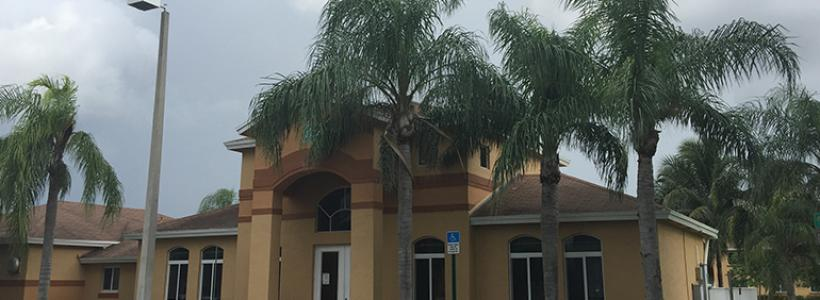 One story light brown building with bushes and palm trees in front of a parking lot.