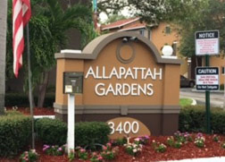 Large brown Allapattah Gardens entry sign surrounded by red mulch, small bushes and flowers.