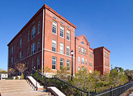 The historic, restored, red-brick Arlington School with landcaping in front and a stairway leading to the other parts of the community.