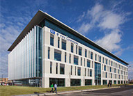 Artist's rendering of BJC Commons, a beige and blue-glass office building.