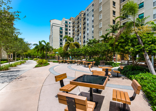 Patio tables outside in the courtyard and walkway area with palm trees and landscaping around it and a multi-story beige and yellow apartment building in the back.
