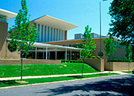 The front of COCA, showing the original mid-century modern building with a deep roof overhang, interior courtyard, sidewalks and tree lawns.