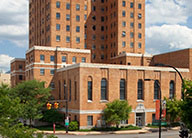 Canal Square, the former historic YMCA, is a multi-story, orange brick building with stone details and large windows on the ground floors.