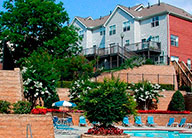 View of the pool at Centennial Place, with blue pool chairs and a stairway leading up to an apartment building on the hill behind the pool area.