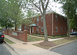 A rectangular two story red brick building with equally spaced windows surrounded by many trees.