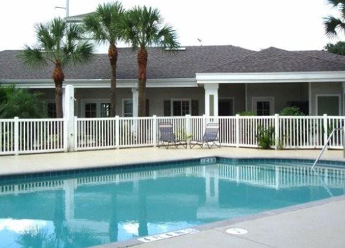 A simple pool surrounded by a white fence in front of a one story white building with many windows.