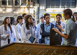 Picture of several youth in lab coats and some in safety googles listening to an young adult instructor in an industrial-looking space.