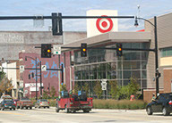 A view of the East Liberty Target from across the street, showing a streetlight and cars and the glass and metal building with a large Target sign.