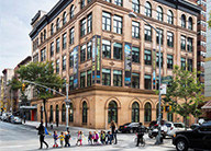 A street view of the Educational Alliance of New York City historic building with large, arched windows on the ground floor and children crossing the street in front of the building.