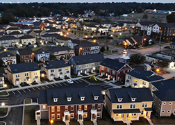 Aerial photo at dusk with various two-story townhome apartment buildings.