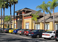 Photo of Irvine Inn main entrance in orange and red stucco, with palm trees, sidewalk, and front parking lot with cars.