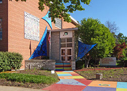 Exterior entrance to Jefferson Elementary School with a brightly-stained, multi-colored sidewalk leading to the front door with large, blue, triangular scultpures on either side of the door.