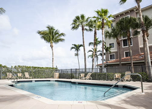 View from the across the outdoor pool with handrails and beige pool chairs enclosed by a black metal fence. Palm trees and shrubs behind the metal fence and a five-story beige and brown apartment building in the background.