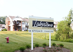 A white and black Lakestone sign on two tall white pillars surrounded by dark mulch and a crescent of very small bushes, in the background is a two story apartment building.