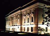 The historic Lewis Center lit up at night with uplighting highlighting the classical features of the building, including pediments over windows and pilasters in the walls.