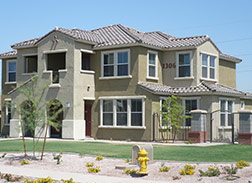 A light brown two story stucco building with tiled brown roof and many windows. The front lawn has a light gravel area with a sidewalk and a yellow fire hydrant.