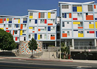 A five story modern white building with many panels of bright orange, yellow, and blue around the windows.