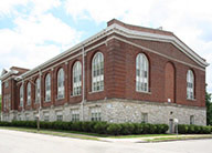 A view of the historic brick building with large, two-story arched windows and a stone foundation.