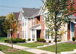 Streetscape showing attached townhouses in yellow and red brick with white trim, gables and paths from doors to sidewalks with street trees.