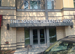An entry way of two gray doors with white lettering above that says The Nannie Hellen AI 4800. The doors belong to a light beige brick building with at least two floors.