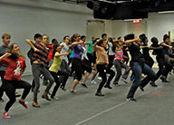 A large group of people of all ages dancing in lines in a studio at the National Dance Institute.