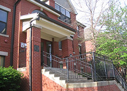 The entryway of a red brick building with a large L shaped concrete and brick staircase leading up to the front doors. There are trees lining the staircase.