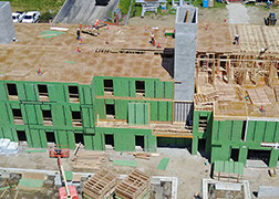 Aerial view of a three-story building under construction. The building is wrapped with green protective material.