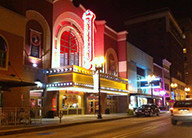 Nighttime view of historic-style theater with large lighted marquee and neon vertical sign.