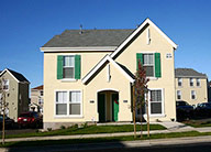 A standalone light beige two story building with windows with green shutters.