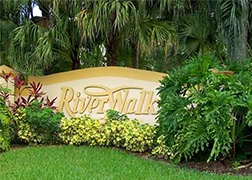 A beige RiverWalk sign surrounded by small bushes, a medium bush, and backed by medium sized palm trees, all on a green lawn.