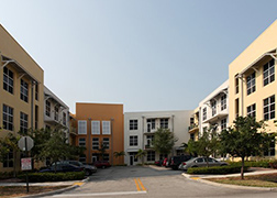 Front view of two-story, beige, pale yellow, and orange apartment buildings attached to each other forming a