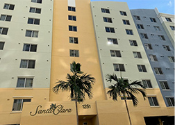 A tall stucco apartment building with many stories and many windows, the exterior is comprised of tan, pale green, and muted blue sections. There are two palm trees in the foreground.