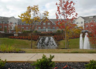 A landscaped fountain with a small waterfall and tall fountain sprays. There are multiple trees turning orange for fall. In the background is a multi-story red apartment building with many windows.