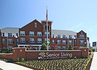 A red brick Senior Living sign with many tiny plants in front. In the background is a three story red brick and white apartment building with many windows.