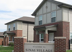 A red brick and tan stucco Welcome to Sinai Village sign in front of two standalone two-story houses with red brick front on the first floor and beige panels elsewhere.