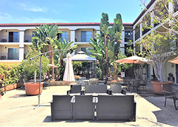 View of the courtyard with three-story apartment buildings surrounding it. The courtyard has patio couches, umbrella tables and chairs, a white tent, potted plants and palm trees.