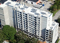 Aerial view of tall, contemporary, concrete multi-story apartment building