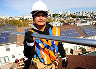 Construction worker wearing hard hard and holding metal pipe with roofs containing solar panels in the background.