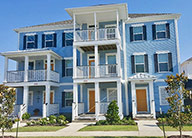 A row of three blue three-story townhomes. The middle one has a white balcony on every floor and the left one has a balcony on the second floor, all three have covered patios. They each have small front lawns.