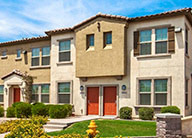 Two story light beige townhomes with red doors. Each townhomes has multiple windows, some with brown shutters. There is a a small green lawn.