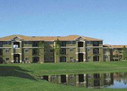 A three story gray apartment building with shallow brown roof on a green lawn with a pond.