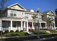 A row of two story townhomes with a light beige and white exteriors. Each has a covered patio and a small lawn with small bushes along the patio fence.