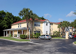 Corner view of two-story beige and white siding with a red shingled roof, two awnings with columns and a porch underneath, a parking lot with a few sedan parked cars, palm trees and trees in the back.