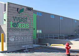 Industrial metal-sided building with sign for the West Texas Food Bank.