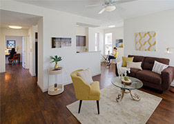 A Legacy Pointe living room with brown sofa, yellow chair, round glass coffee table, pictures on wall, floor lamp, dark floor and cream rug, looking back into the kitchen and back hall.